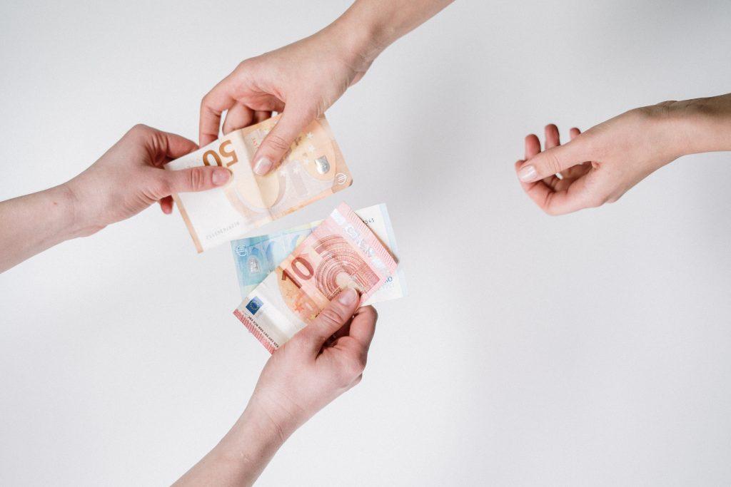 Quattro mani che si scambiano soldi euro